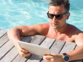 Un homme dans une piscine avec une tablette tactile